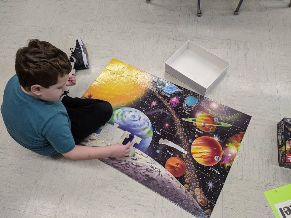 Michael Gelenius Works on a Solar System Puzzle - Mrs. Kellogg's Class