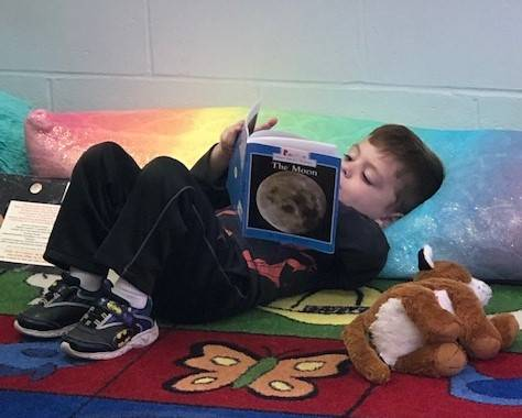 Tiny Toppers student reading a book.
