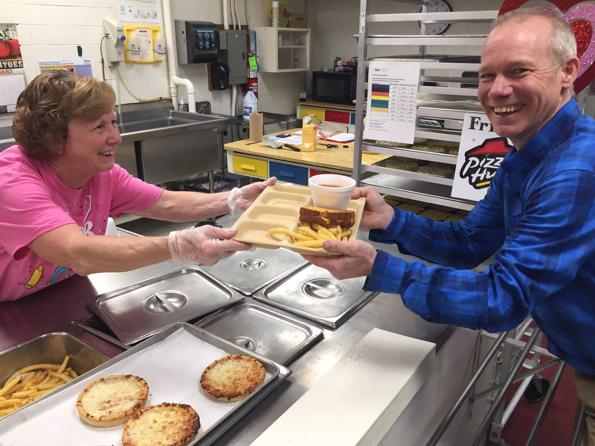 Food Services Staff Member Mrs. Peine serving lunch on a tray to Mr. Mullaly