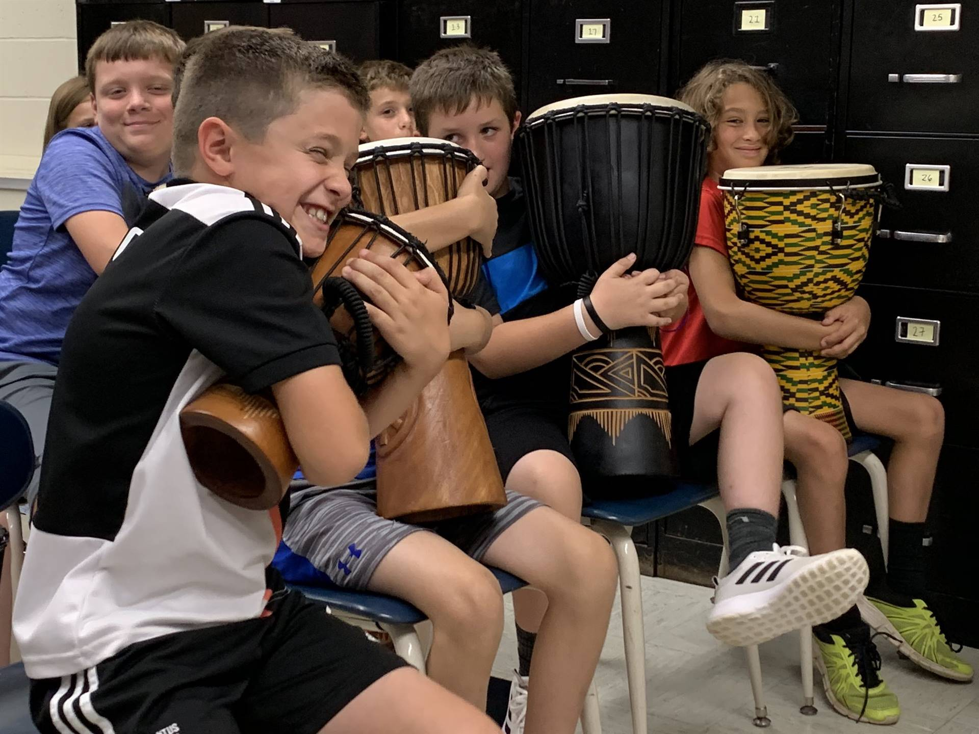 Photo 9:  CMS students smiling and hugging djembe drums during music class.