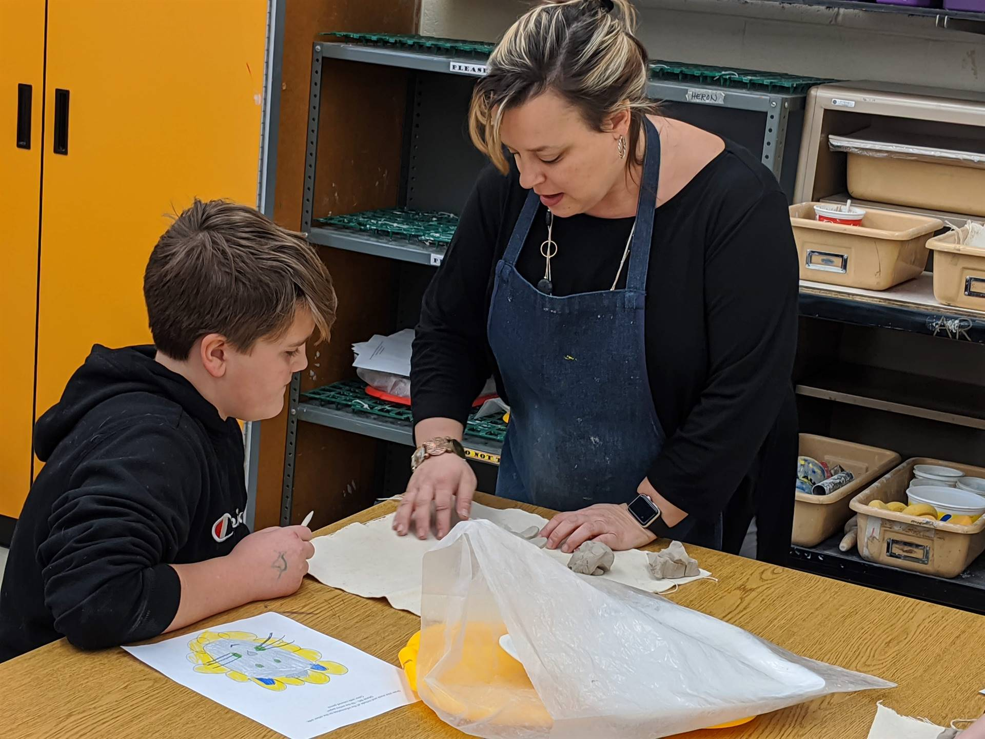 Photo 4:  CMS art teacher Ms. Heron assisting a student with his art project.