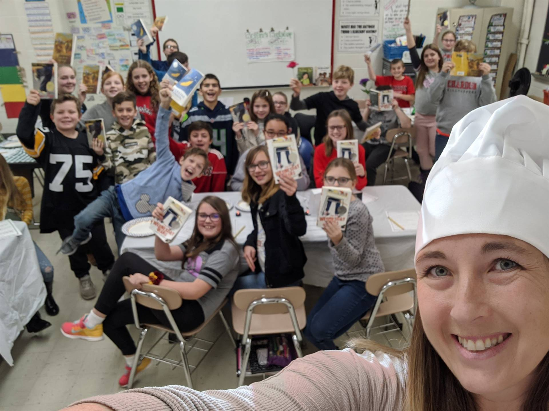 Photo 6:  English Language Arts teacher Mrs. Monsman wearing a chef's hat with her students all