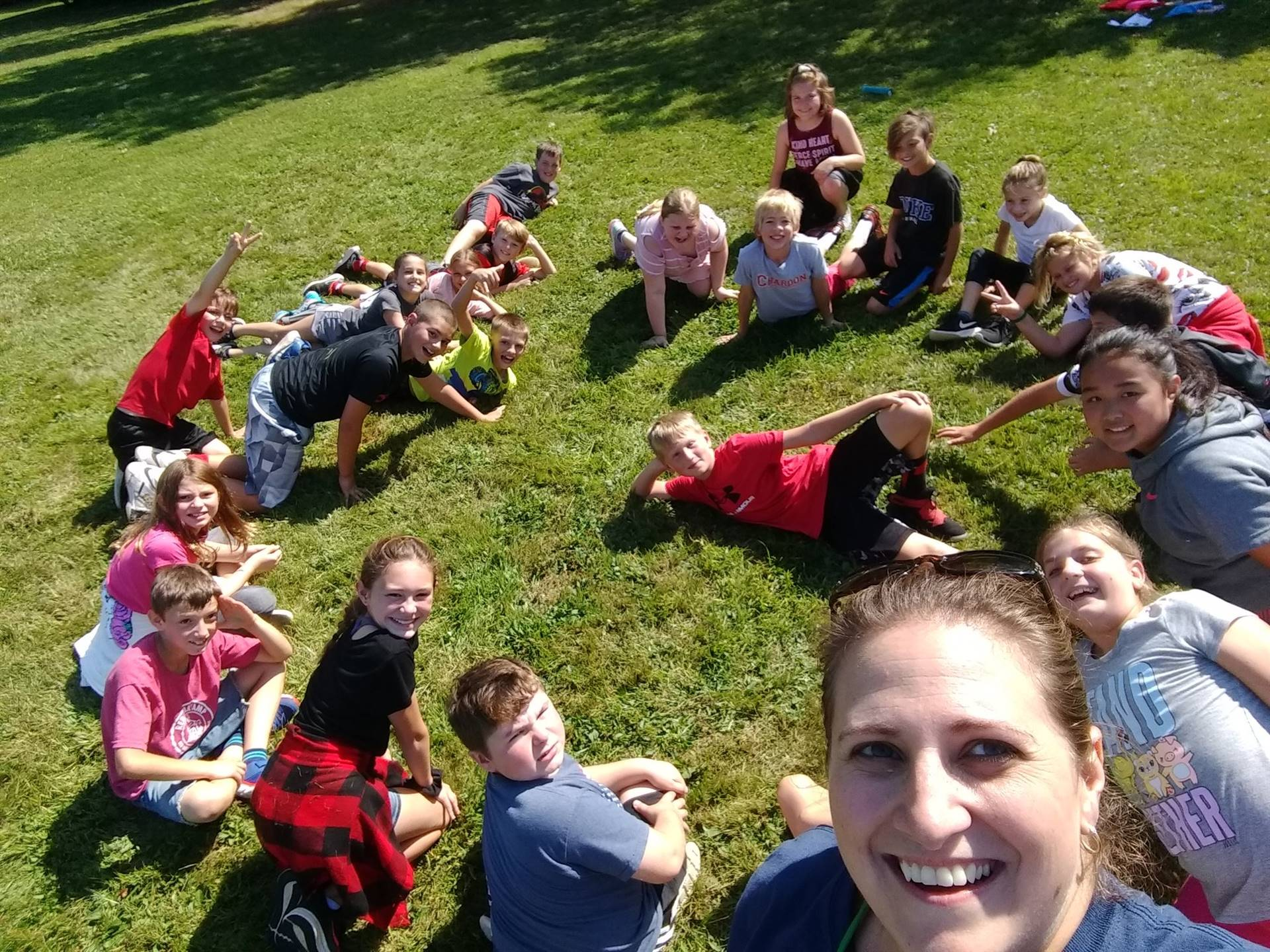 Photo 2:  CMS math teacher Mrs. Mele with her students gathered outside on the grass for Field Day 2