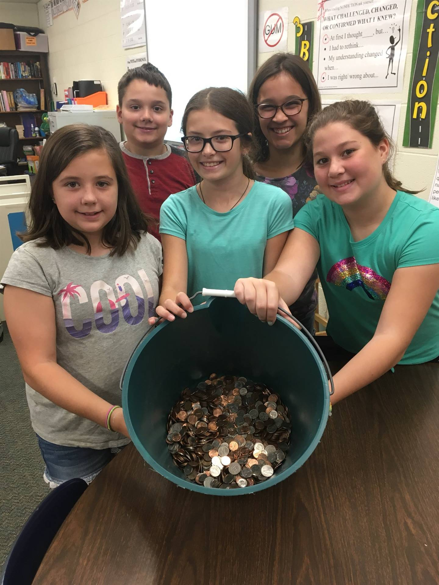 Photo 3:  5 CMS students gathered together and smiling with a bucket full of coins collected for the