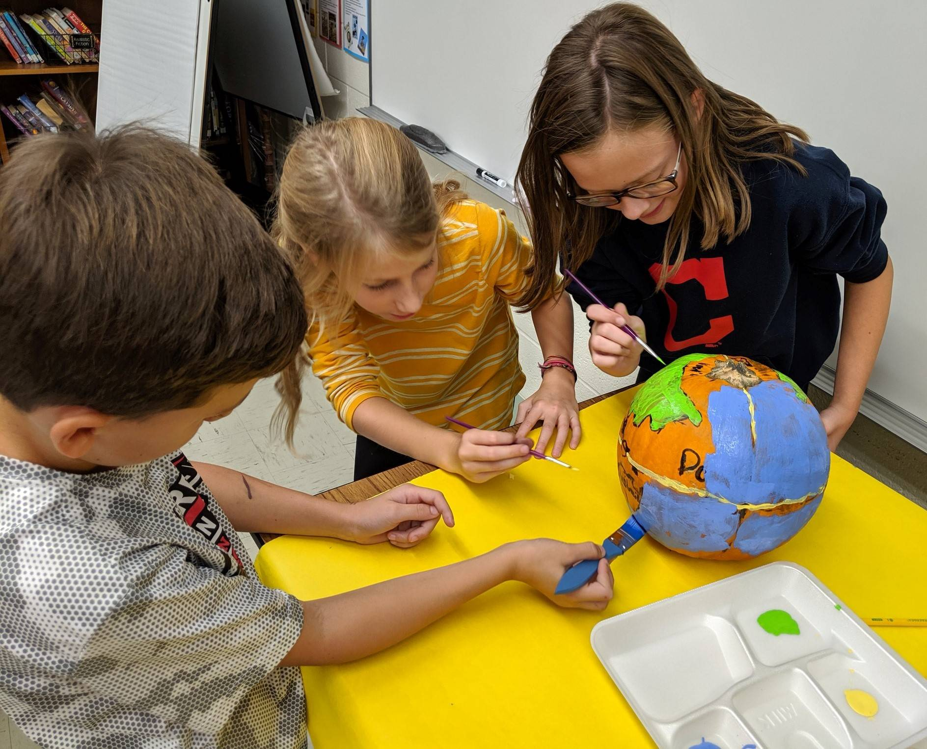 Photo 1:  3 CMS students each (together) painting a pumpkin to look like a globe.