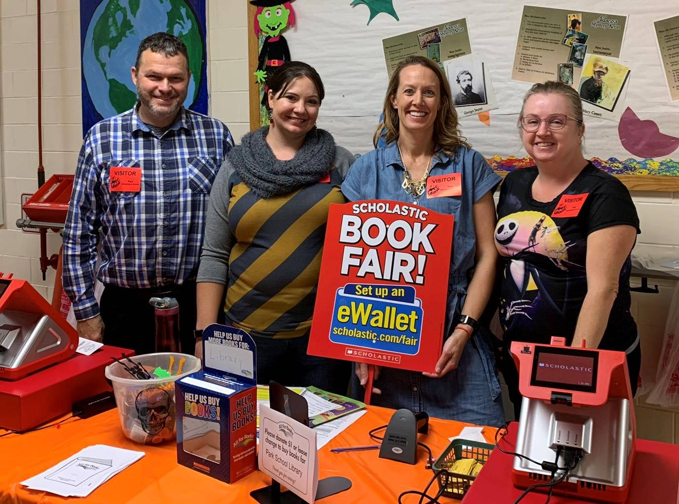 Photo 2:  4 parents volunteering at school Book Fair - standing at table holding up a Book Fair sign