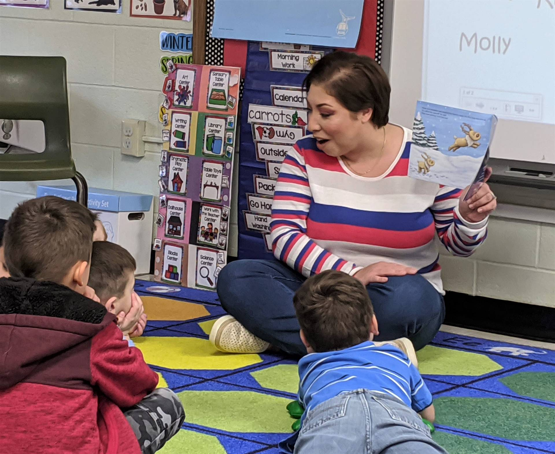 Photo 1:  Parent sitting on the classroom rug with students reading a book to Tiny Toppers Pre-K stu