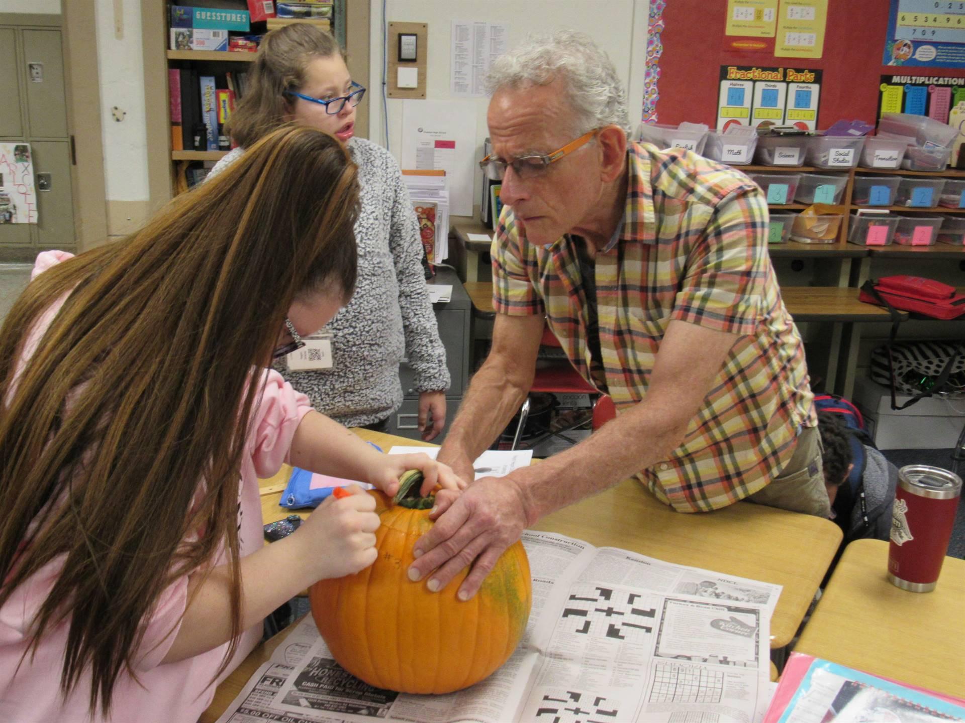 Photo 5:  Parent volunteer helping a student carve a pumpkin at Chardon High School