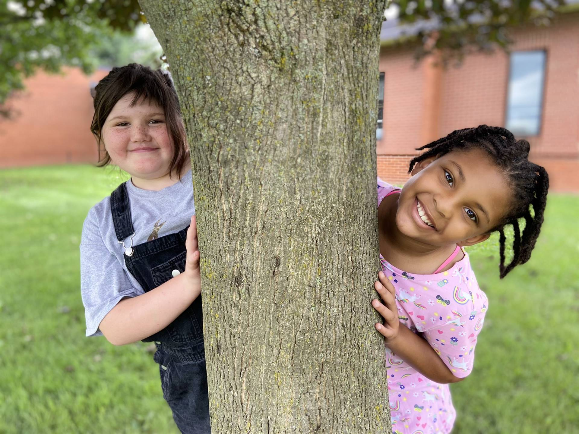 Photo 1:  2 Munson students each on one side of a tree outside at recess smiling for the camera