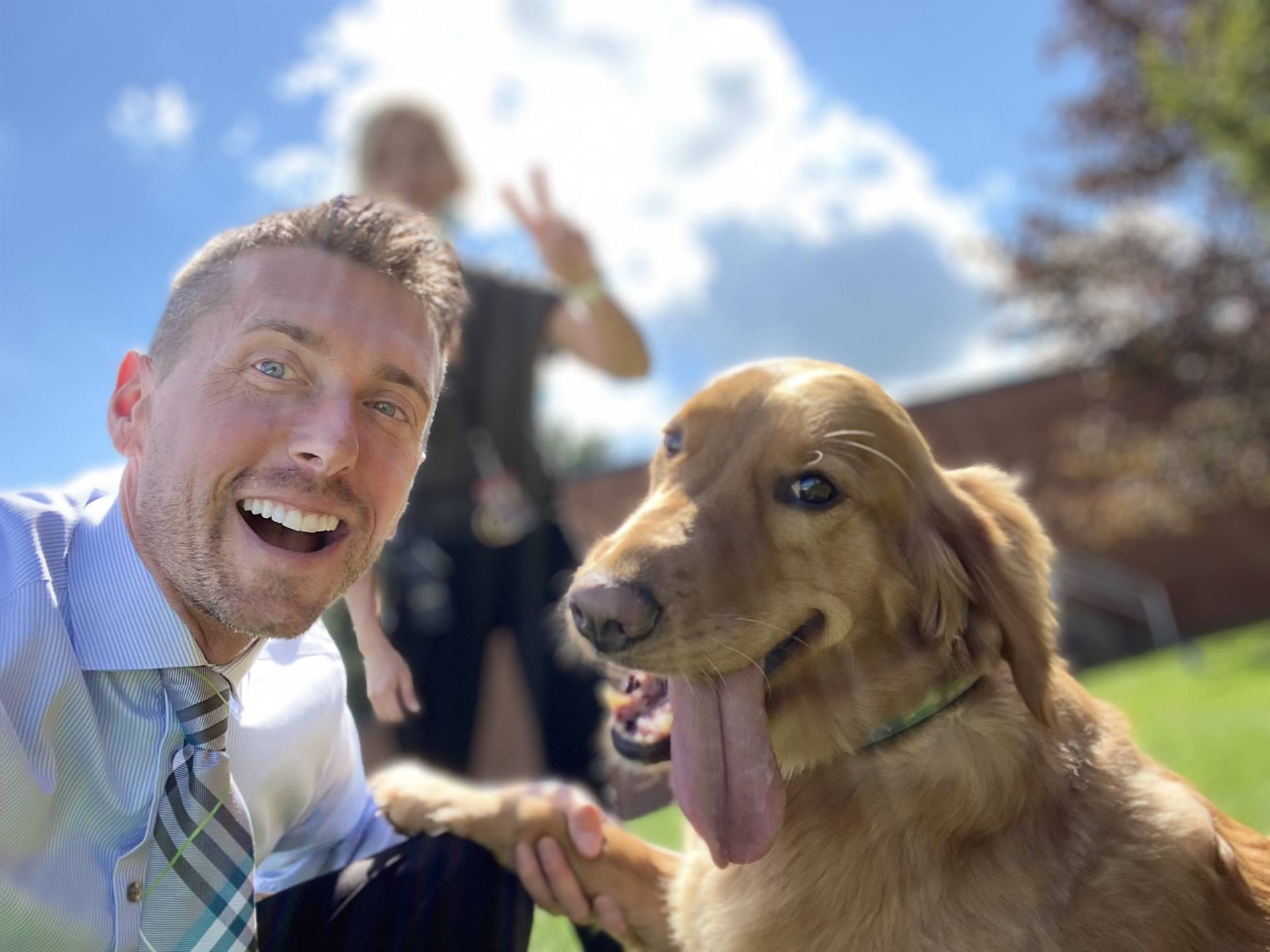 Photo 3:  Munson Principal Prezioso with Honey the Therapy Dog outside on the school grounds