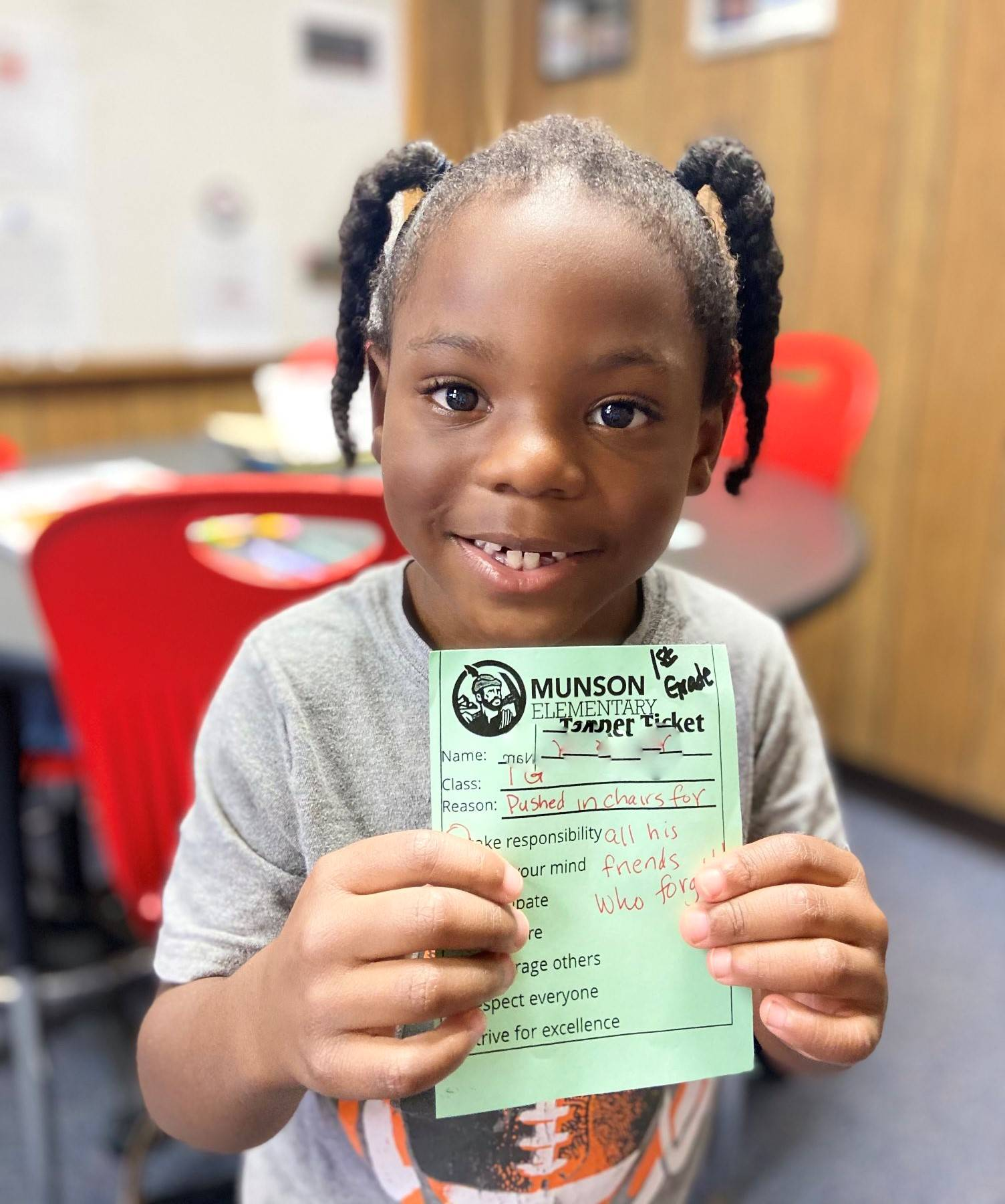 Photo 26:  Munson student smiling for the camera holding a Topper Ticket received for excellent citi