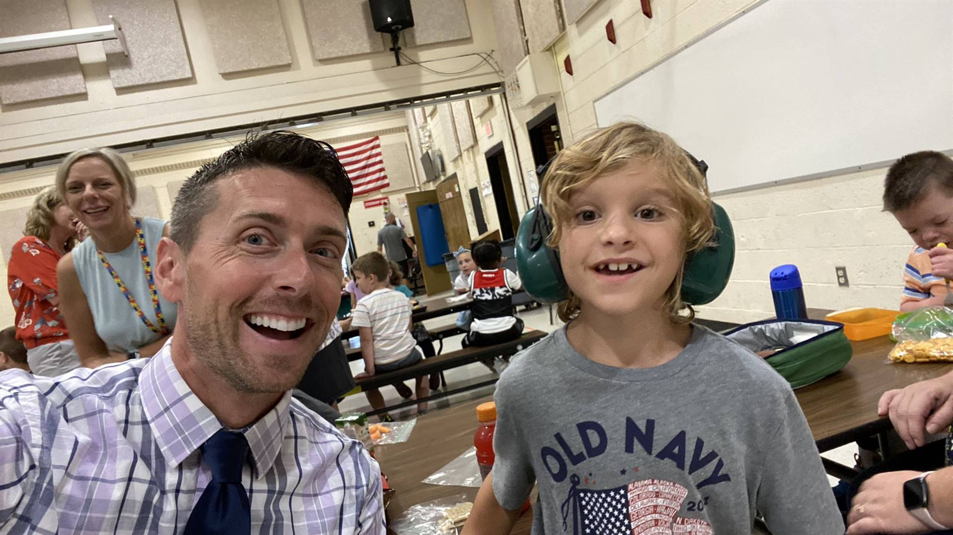 Photo 23:  Munson Principal Prezioso with a student in the lunch room - both smiling for the camera