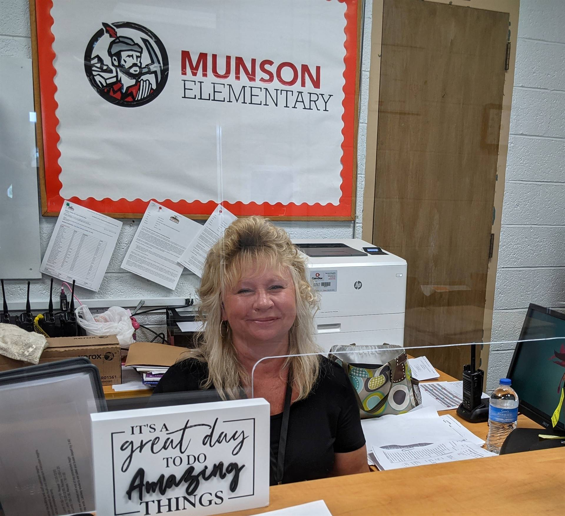 Photo 11:  Munson Secretary Mrs. Sandy Henderson smiling for the camera from her desk in the main of
