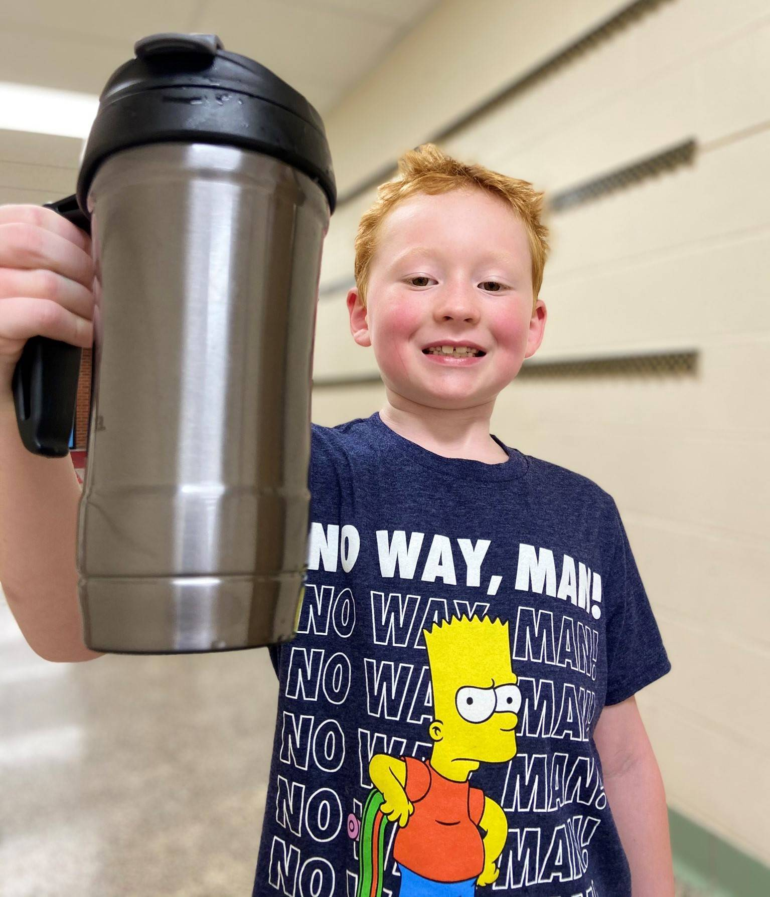 Photo 15:  Munson student holding up a travel mug and standing in the hallway smiling for the camera