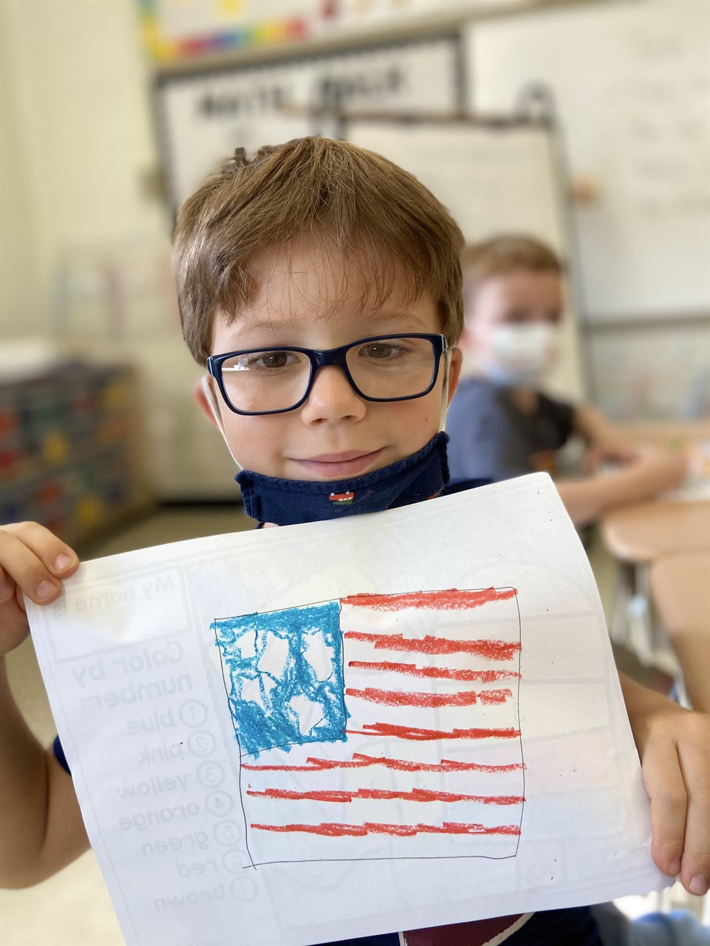 Photo 30:  Munson student standing in the classroom holding up his drawing of the American flag