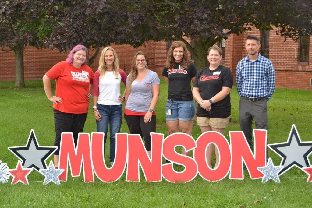 Photo 14:  Munson PTO board members (5) and Principal Prezioso standing in front of a large Munson s