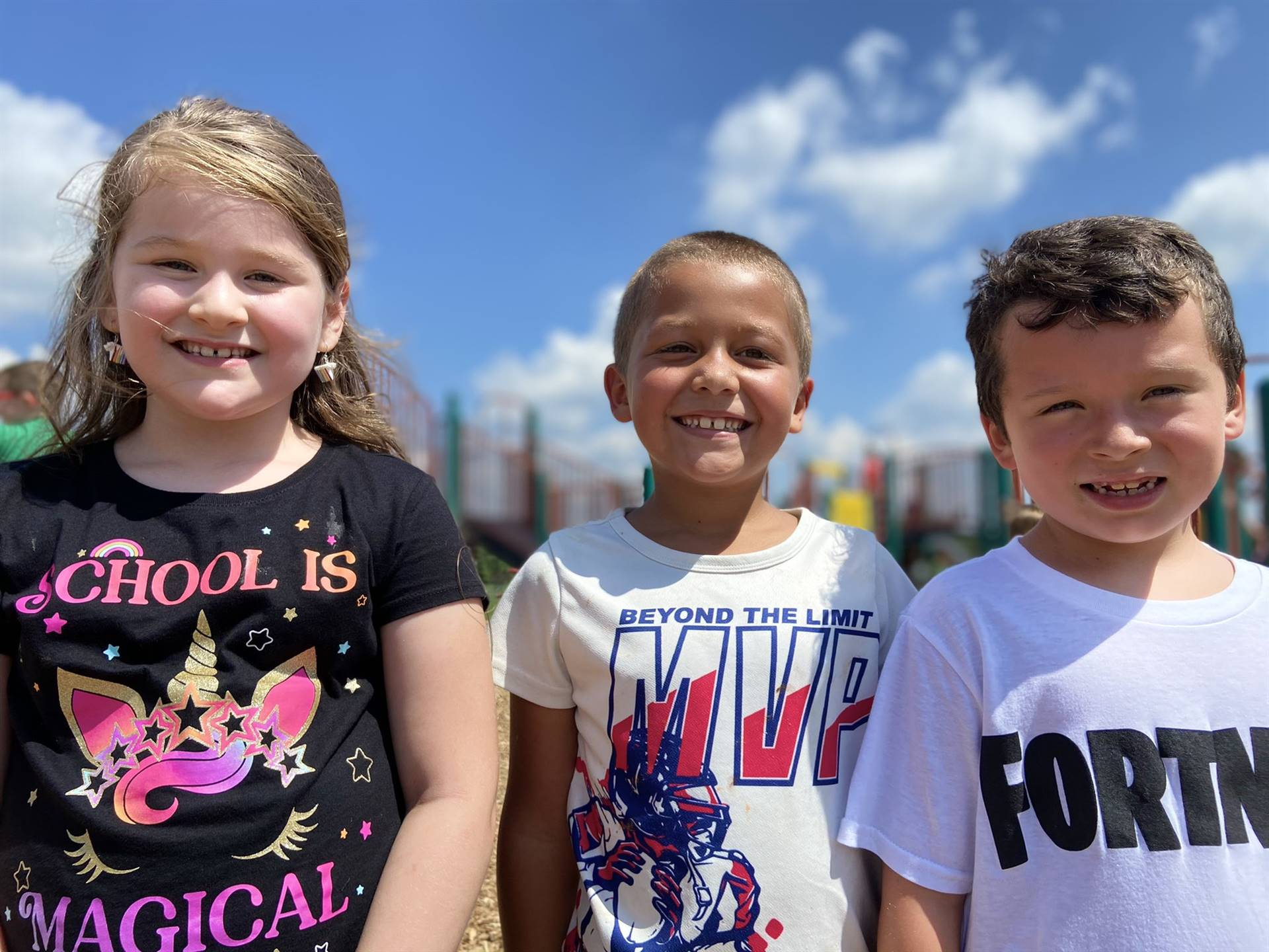 Photo 4:  3 Munson students standing together on the playground on a blue skies day and smiling for