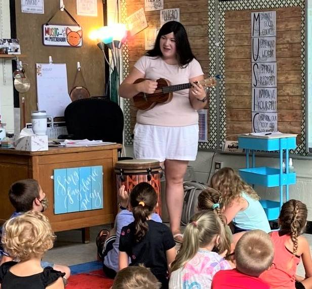 Photo 8:  Music teacher Mrs. Puterbaugh standing in the classroom playing the ukelele as students se