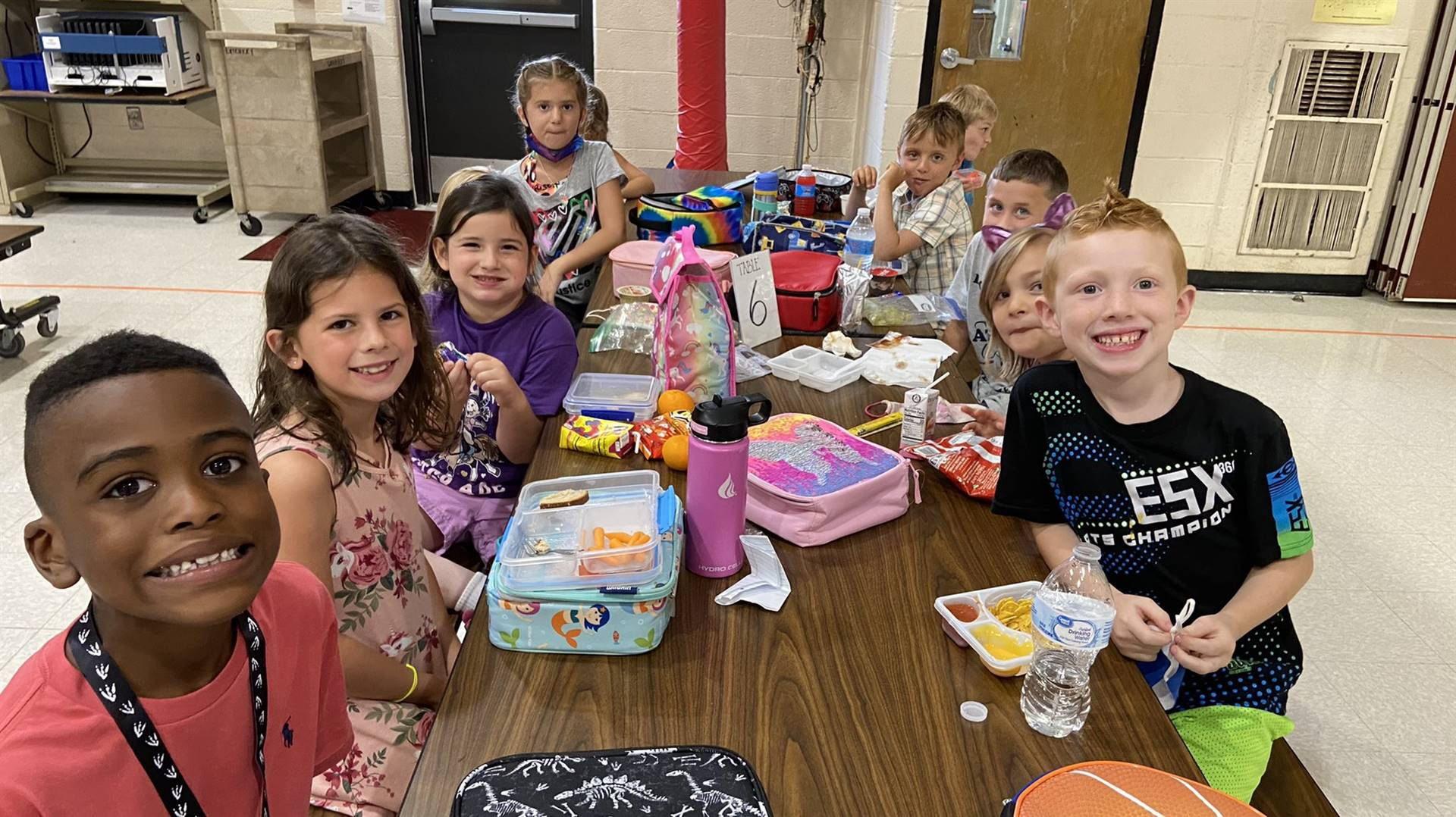 Photo 9:  Munson students at a lunch table during lunchtime smiling for the camera