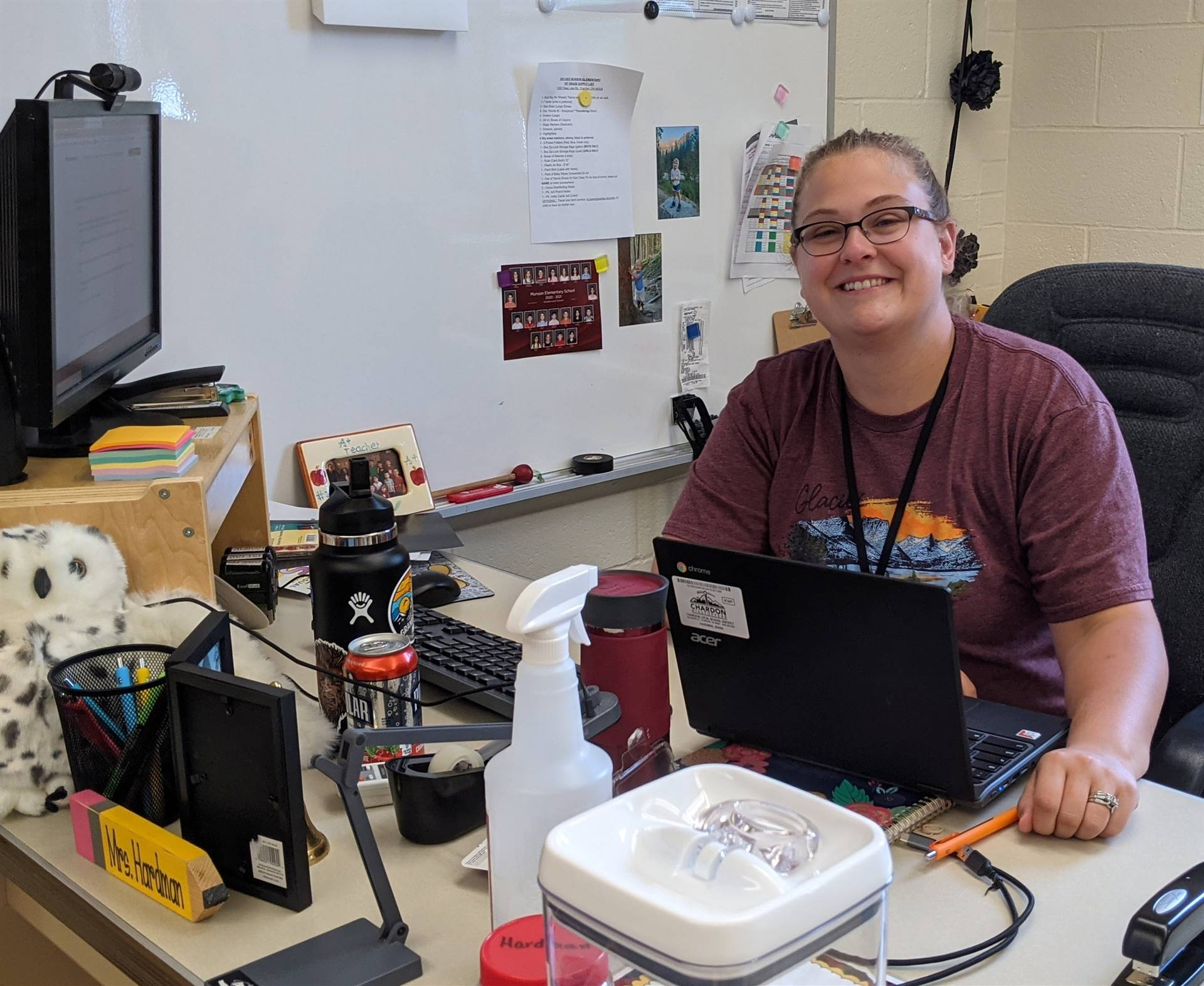 Photo 16:  Munson teacher Mrs. Hardman at her desk and smiling for the camera as she prepares for ba