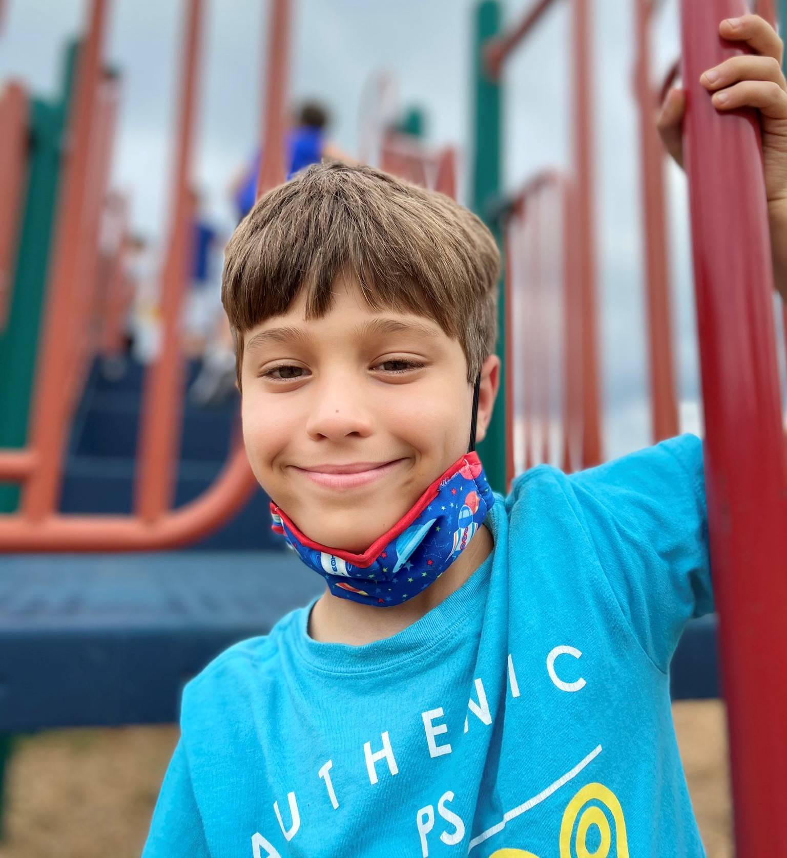 Photo 19:  Munson student on the school playground smiling for the camera