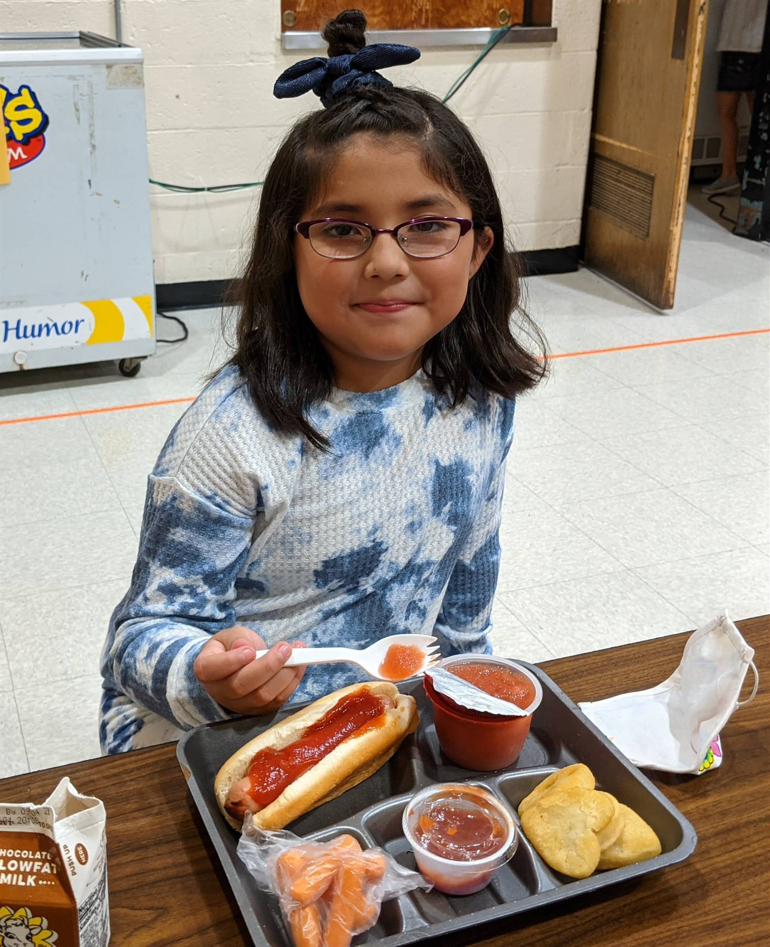 Photo 21:  Munson student seated at the lunch table with her lunch on a tray and smiling for the cam
