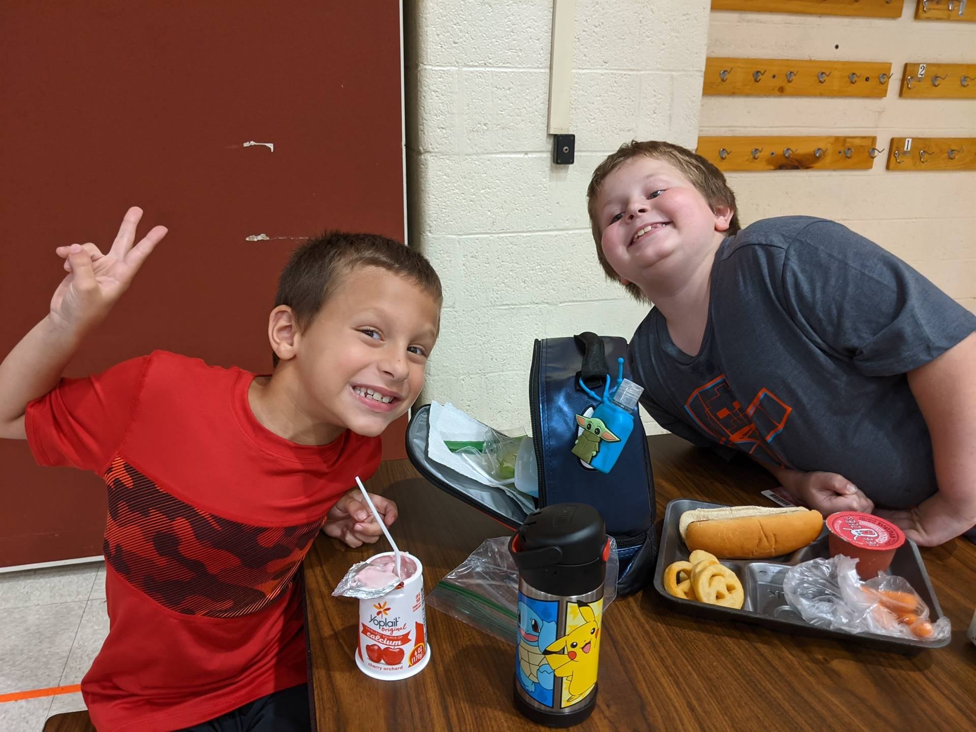 Photo 2:  2 Munson students sitting together at lunch at a table and smiling for the camera - one is